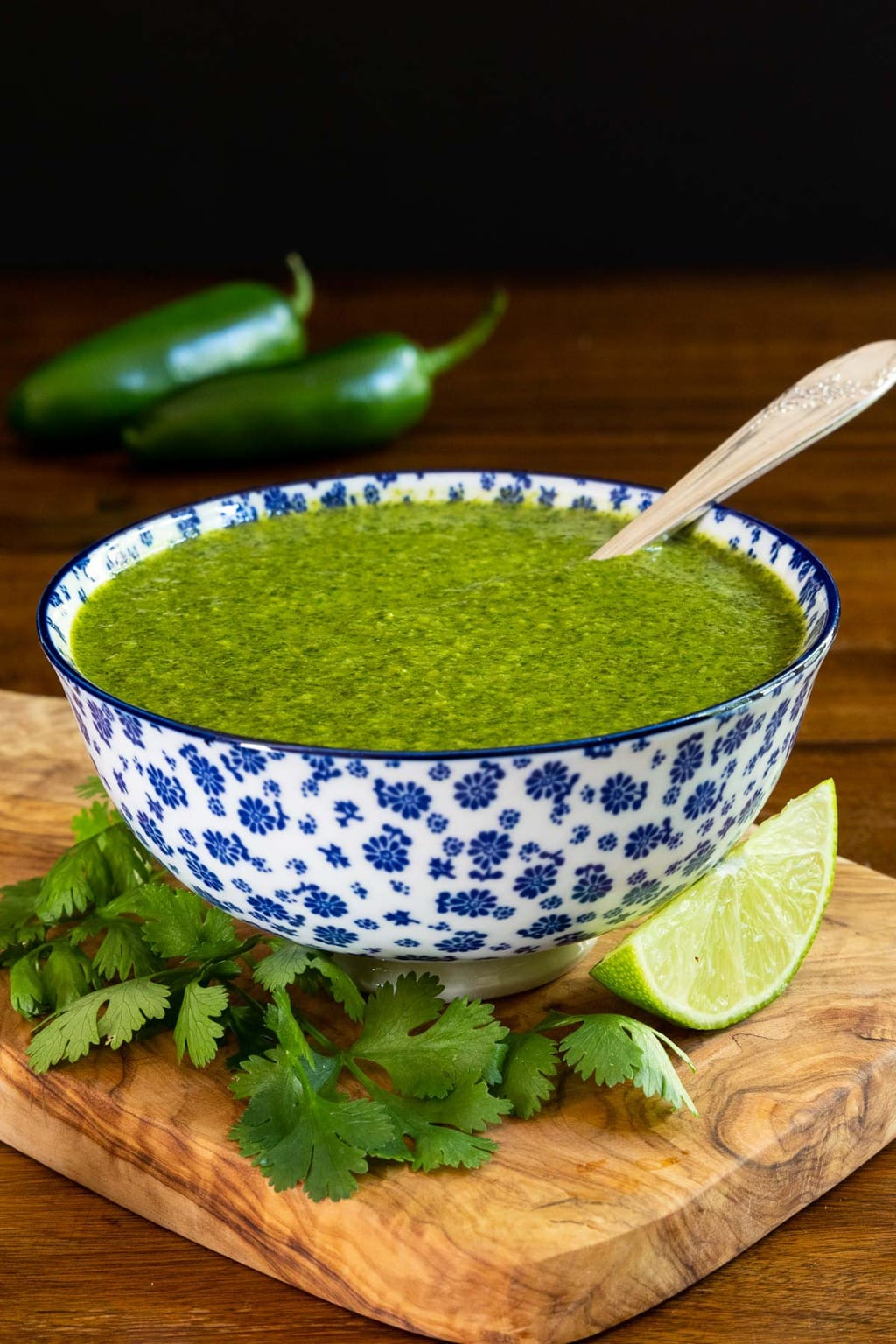 Vertical closeup photo of a serving bowl of Mexican Cilantro Sauce on a wood cutting board surrounded by fresh cilantro leaves and lime wedges.