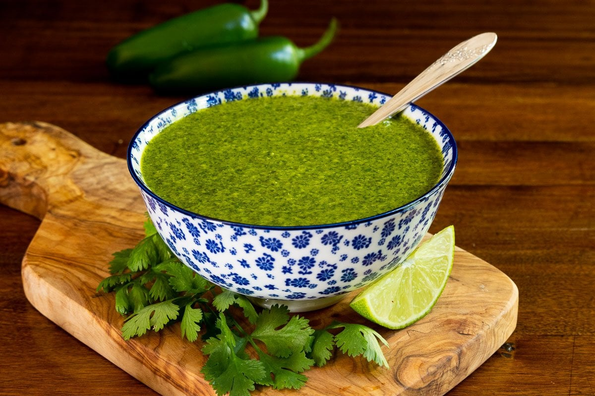 Horizontal photo of a serving bowl of Mexican Cilantro Sauce on a wood cutting board surrounded by fresh cilantro leaves and lime wedges.