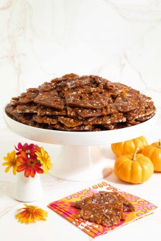 Vertical photo of Sea Salted Pumpkin Pecan Brittle on a white pedestal plate surrounded by mini pumpkins and orange zinnia flowers.
