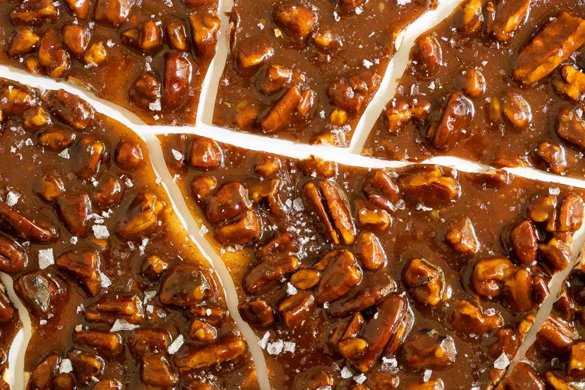 Horizontal closeup photo of Sea Salted Pumpkin Pecan Brittle cracked into bite-size pieces.