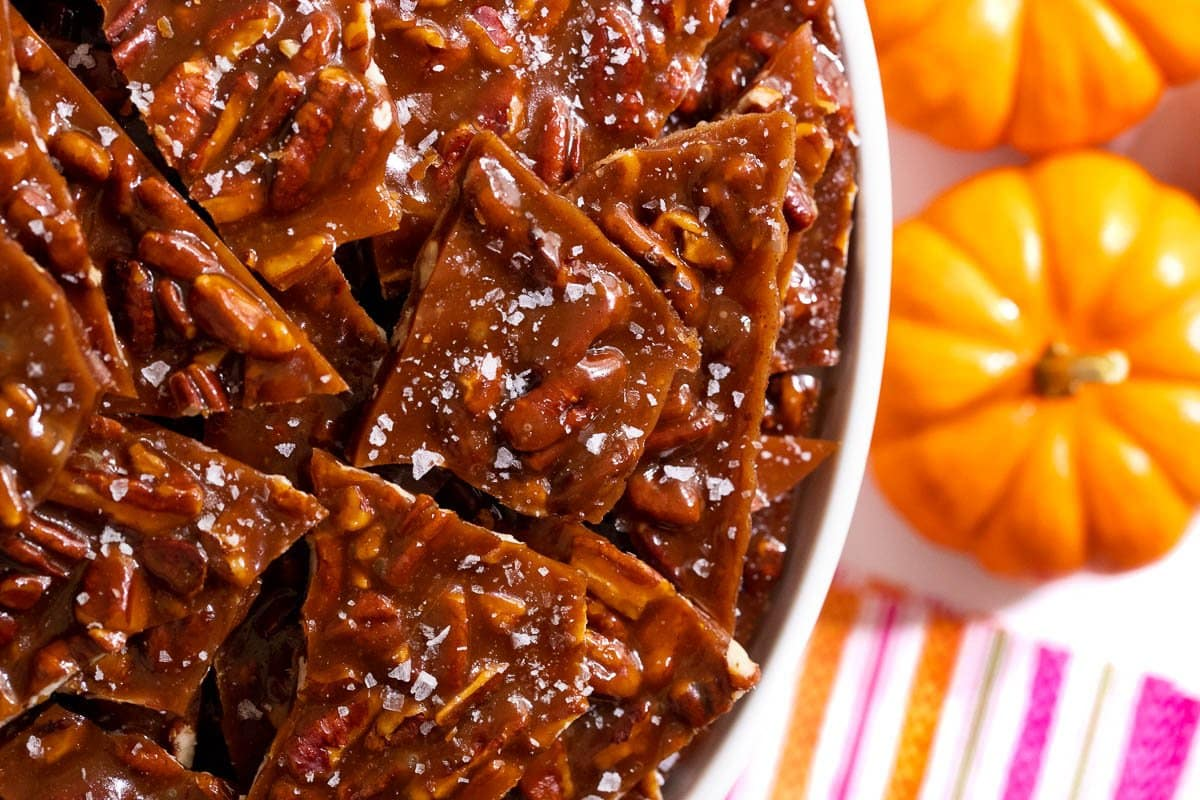 Horizontal overhead closeup photo of Sea Salted Pumpkin Pecan Brittle with mini pumpkins and colorful napkins on the right side.