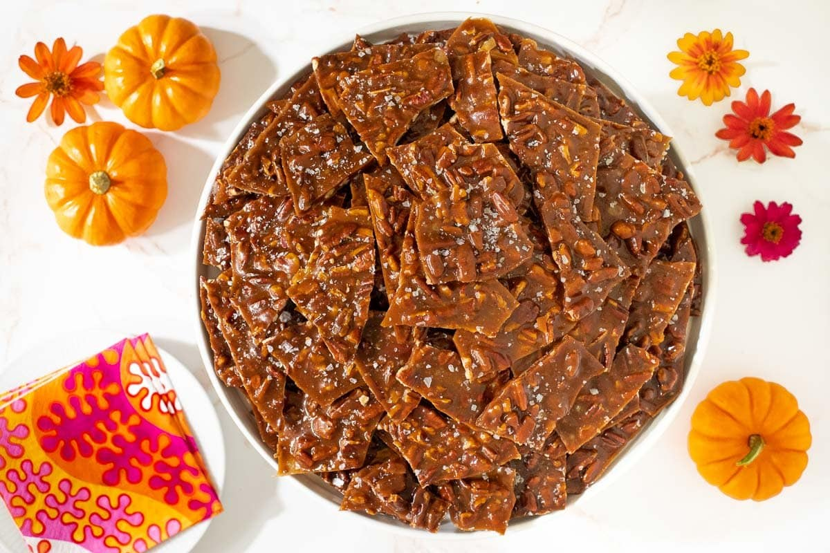 Horizontal overhead photo of a plate of Sea Salted Pumpkin Pecan Brittle surrounded by mini pumpkins and zinnia flowers.