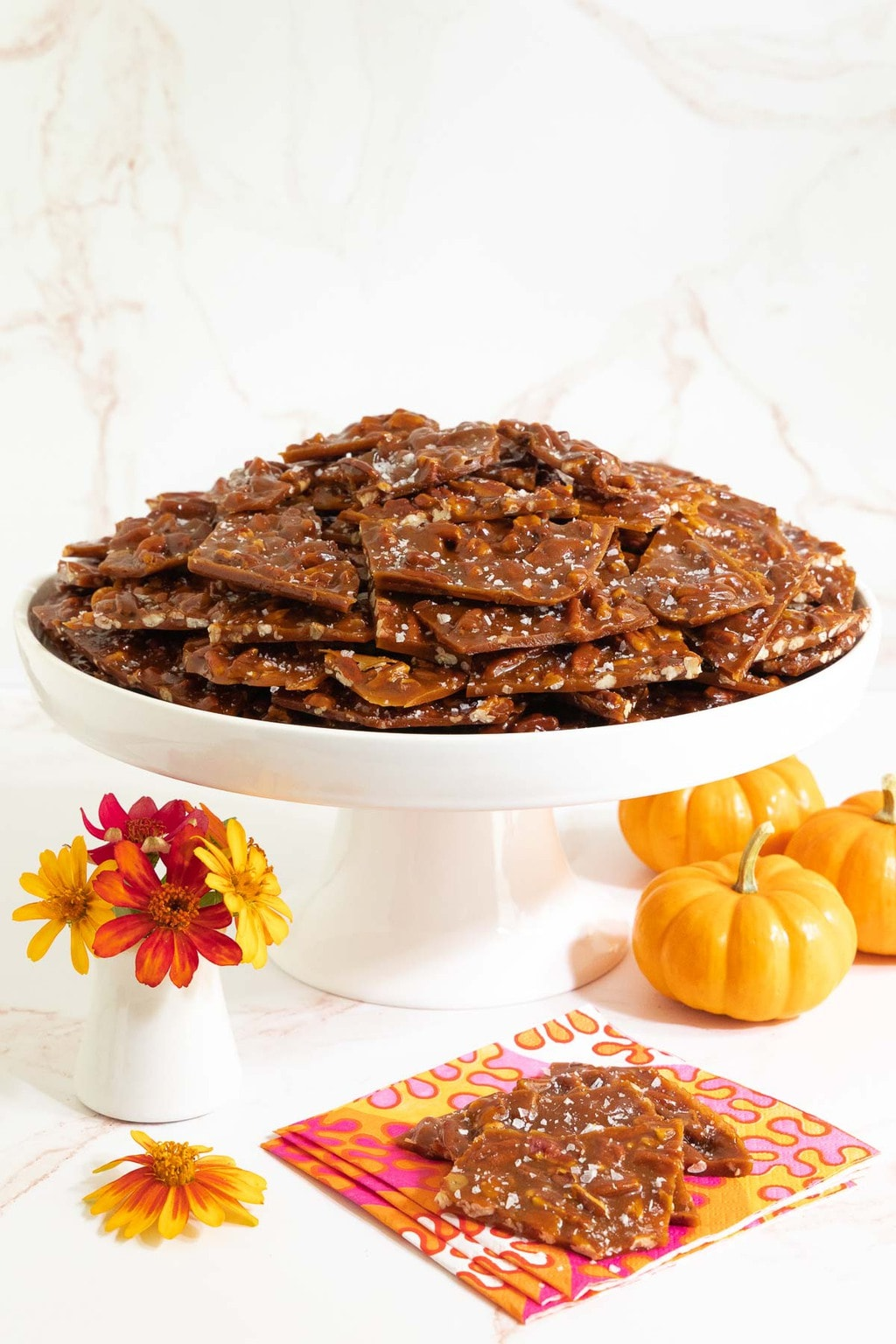 Vertical photo of a white pedestal plate filled with Sea Salted Pumpkin Pecan Brittle surrounded by mini pumpkins and orange zinnia flowers.
