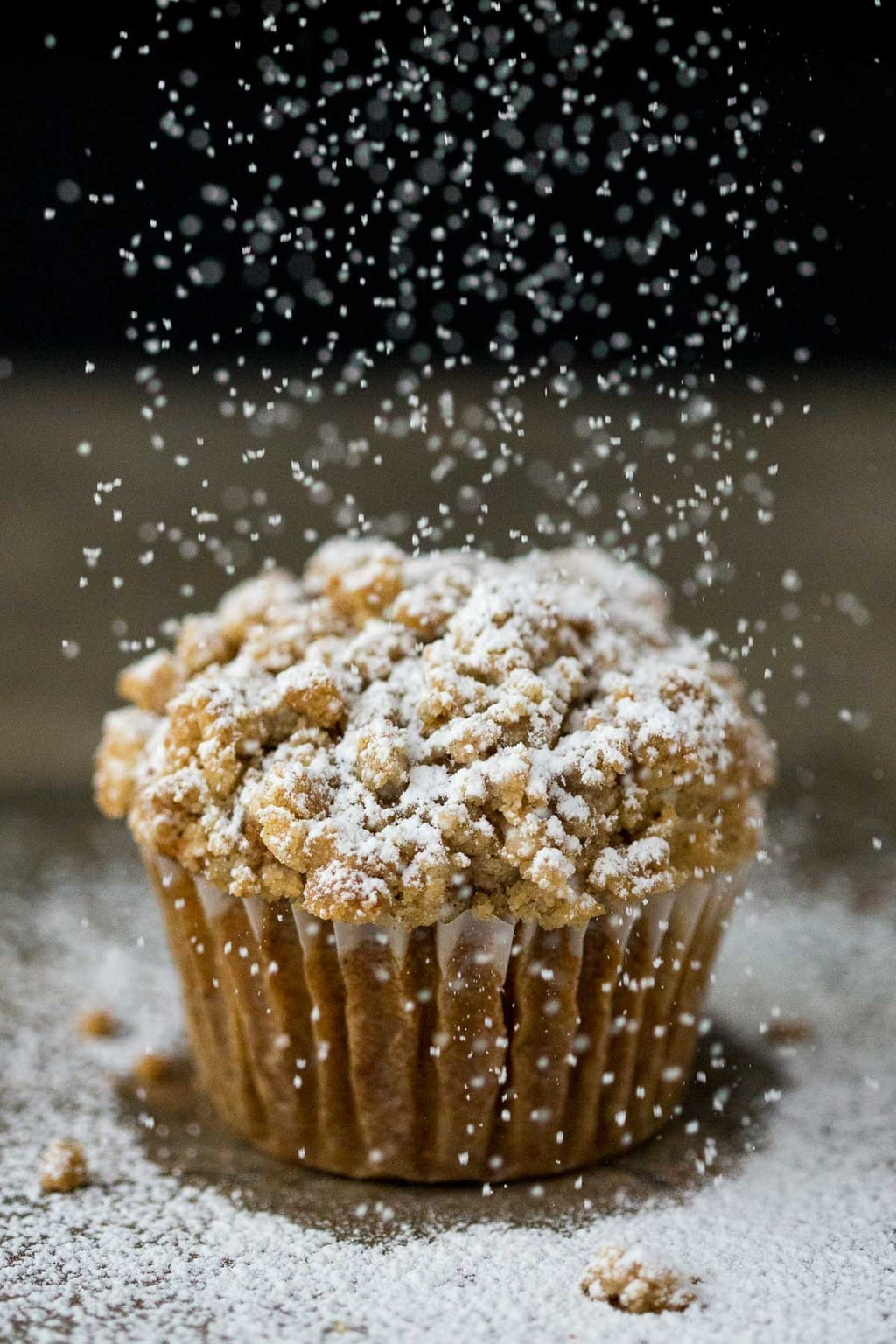Vertical closeup photo of a Pumpkin Crumb Muffin with powdered sugar being sprinkled on top.
