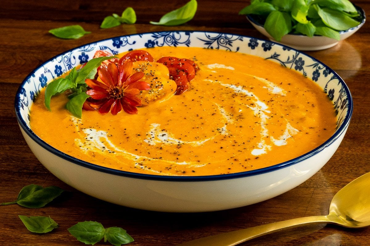 Horizontal closeup photo of a bowl of Creamy Roasted Tomato Carrot Bisque garnished with fresh basil leaves, roasted tomatoes and a zinnia.