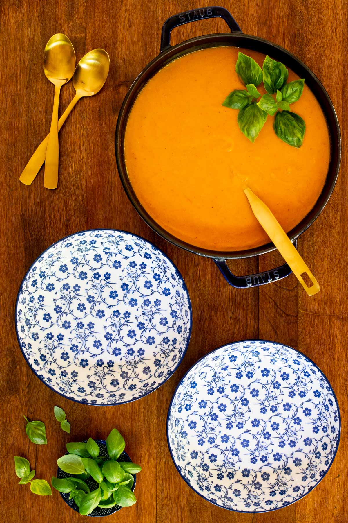Overhead vertical photo of Creamy Roasted Tomato Carrot Bisque on a wood table with two empty serving bowls.