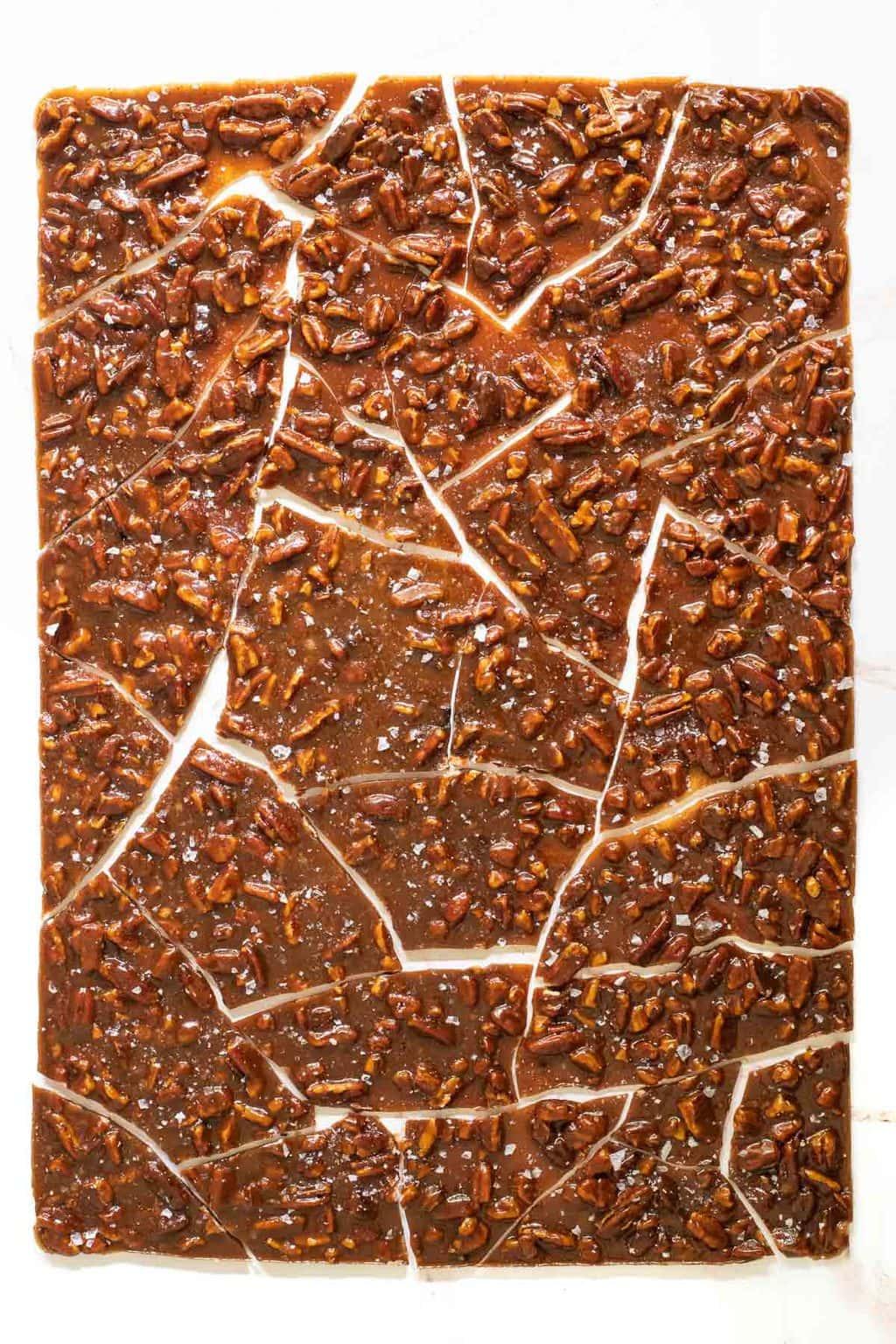 Vertical overhead photo of a baking sheet full of Sea Salted Pumpkin Pecan Brittle broken into pieces.