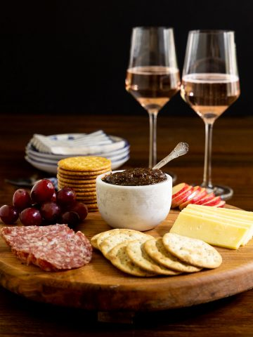 Vertical photo of a wood appetizer tray featuring Sweet and Spicy Fig Spread.