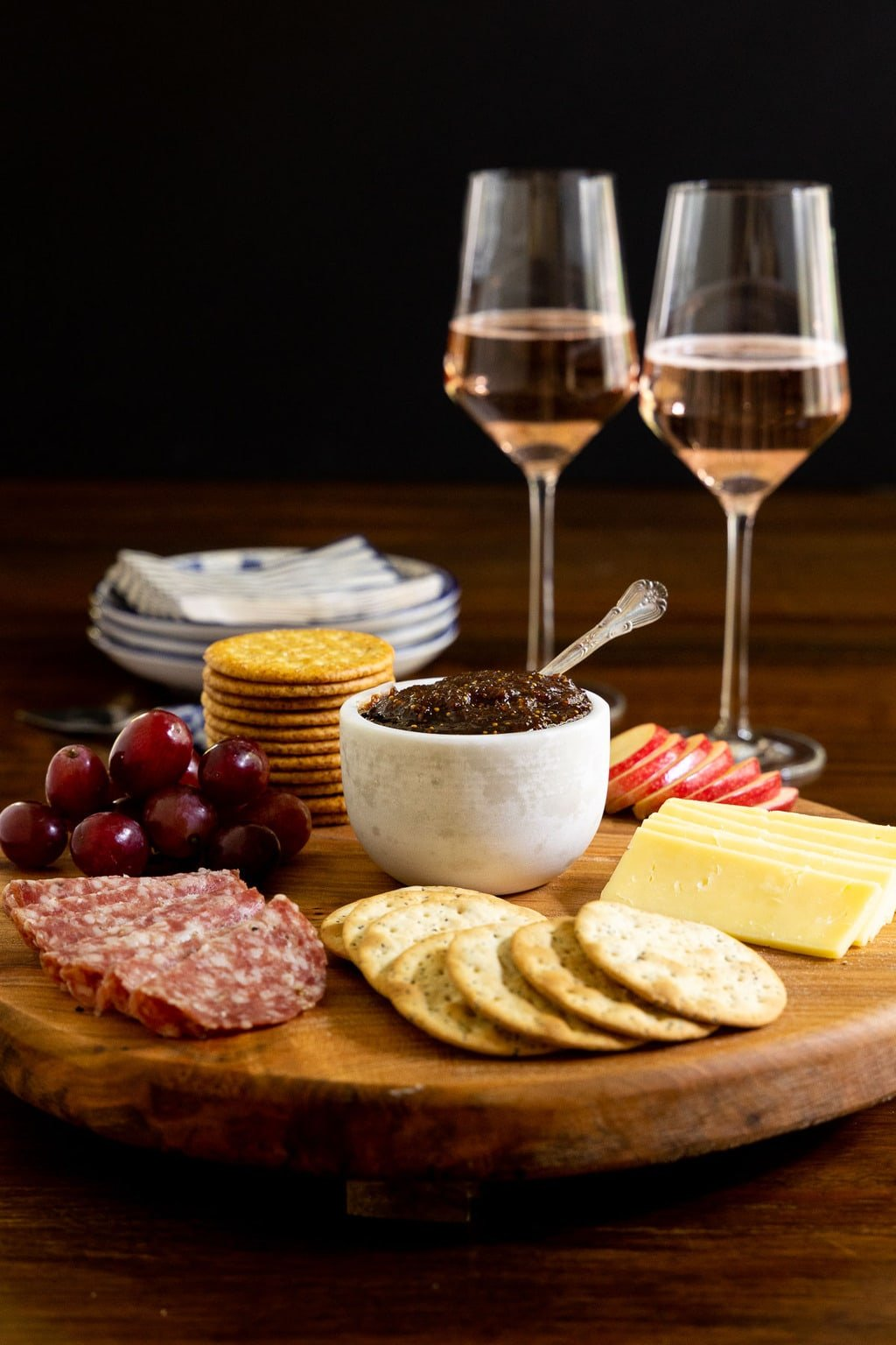 Vertical photo of a wood appetizer tray featuring Sweet and Spicy Fig Spread and surrounded by sausage, crackers, sliced apples, grapes and cheese.