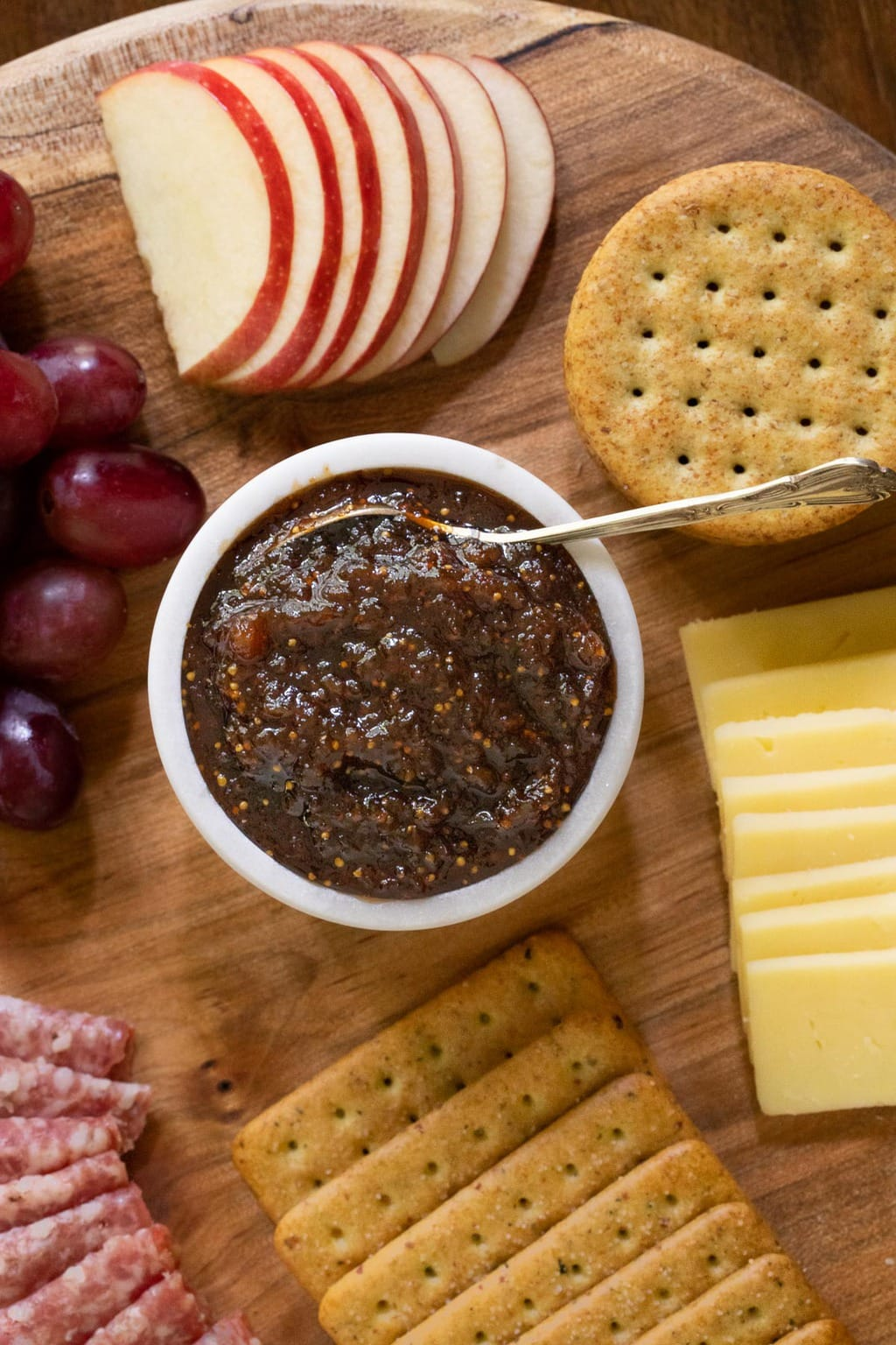Overhead vertical photo of a wood appetizer tray featuring Sweet and Spicy Fig Spread and surrounded by sliced apples, grapes, crackers, cheese and sausage.