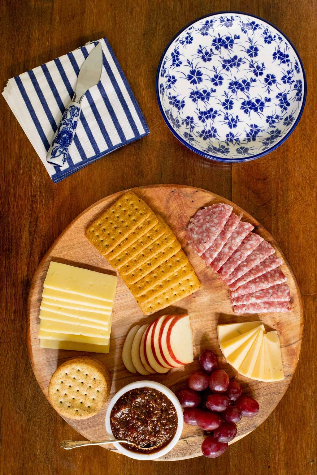 Overhead vertical photo of a wood appetizer tray featuring Sweet and Spicy Fig Spread and surrounded by crackers, slices of cheese and sausage, grapes and sliced apples.