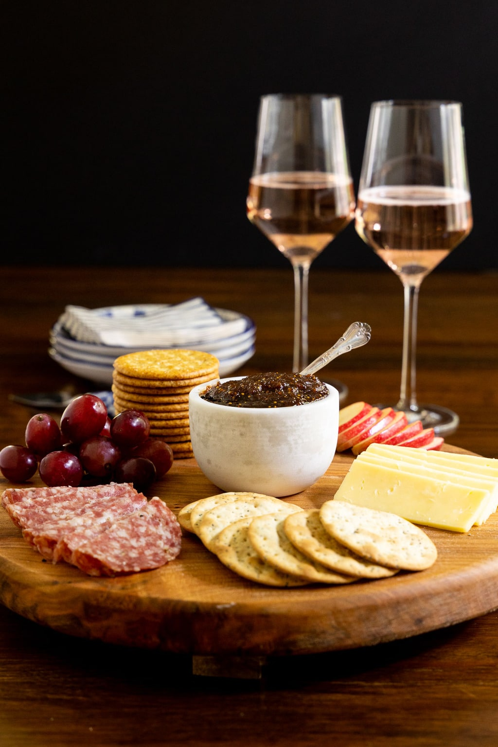 Vertical photo of an appetizer featuring Sweet and Spicy Fig Spread with sausage, grapes, crackers, cheese and apples.