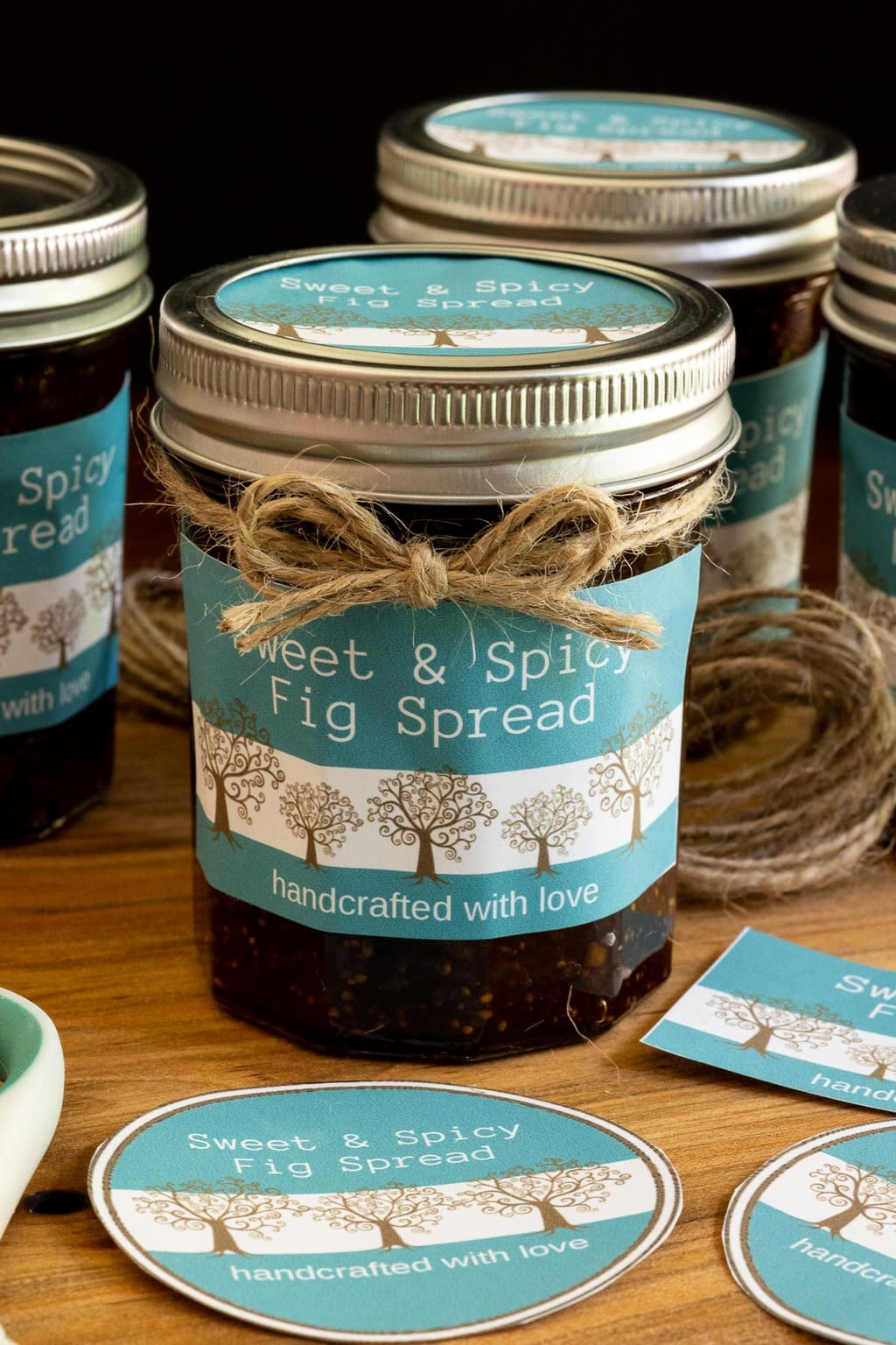 Extreme vertical closeup photo of jars of Sweet and Spicy Fig Spread with custom gift labels and tied with bows of twine.