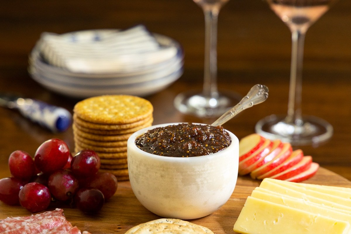Horizontal photo of a white marble cup filled with Sweet and Spicy Fig Spread on an appetizer tray with two glasses of rose wine in the background.