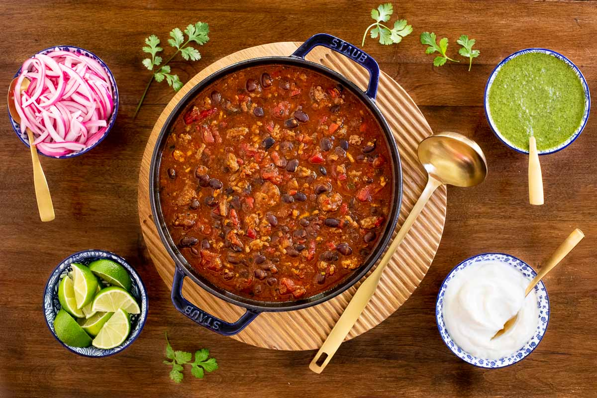 Overhead horizontal photo of a Staub cast iron pot filled with Black Bean Turkey Chili surrounded by cups of pickled onions, cilantro sauce, lime wedges and sour cream.