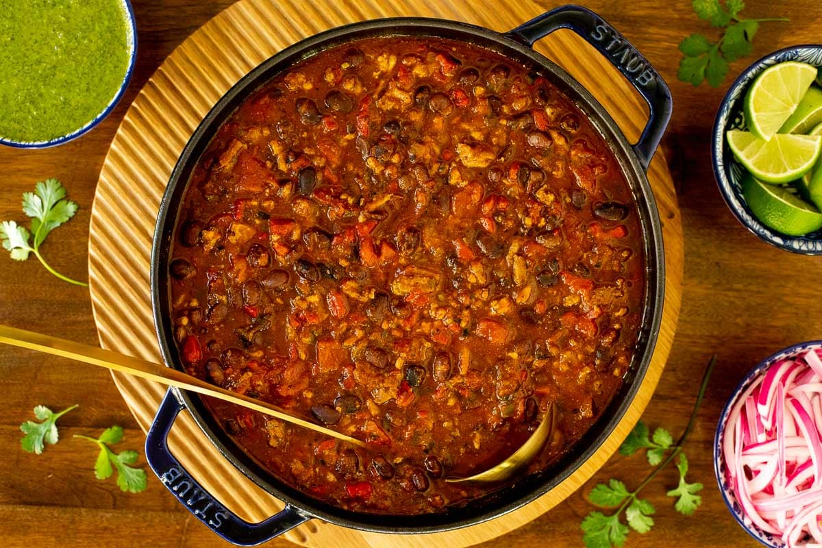 Overhead horizontal closeup photo of a cast iron pot filled with Smoky Black Bean Turkey Chili on a wood cutting board.