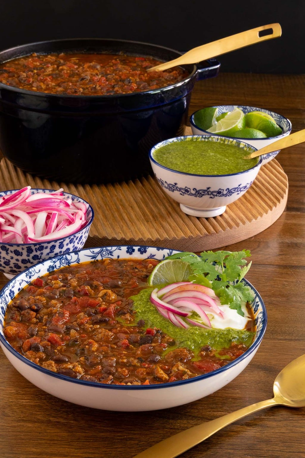 Vertical photo of a serving dish and a pot of Black Bean Turkey Chili garnished with cilantro sauce, pickled onions, fresh cilantro and lime wedges.
