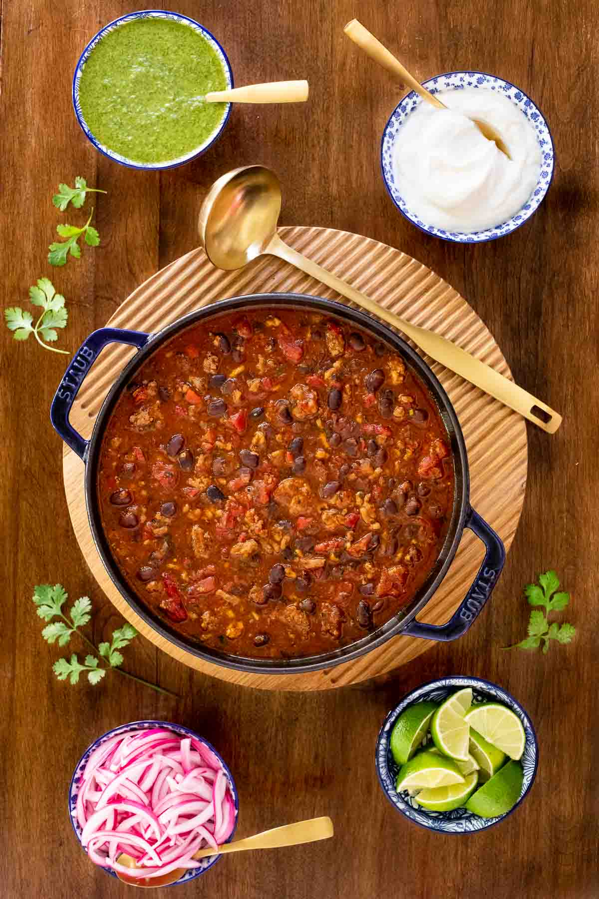 Vertical overhead photo of a pot of Black Bean Turkey Chili on a wood table.