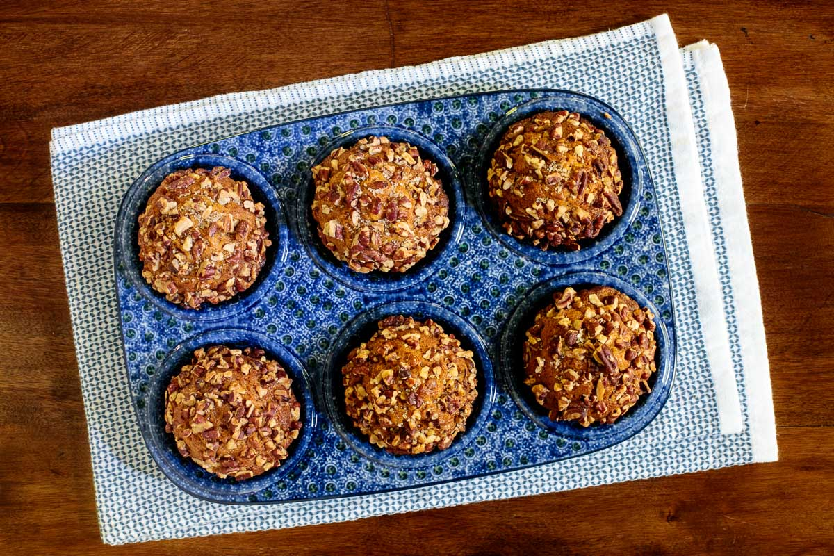 Overhead horizontal photo of a blue muffin pan filled with Easy Praline Pumpkin Muffins on a wood table.
