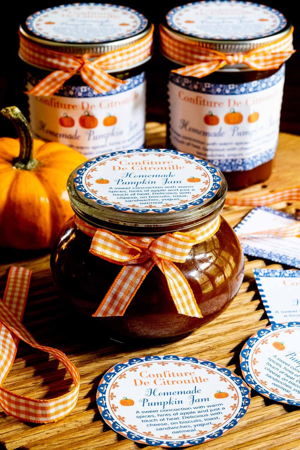 Horizontal photo of a group of glass jars of Pumpkin Jam (Confiture De Citrouille) on a wood tray with custom gift labels for the jam.