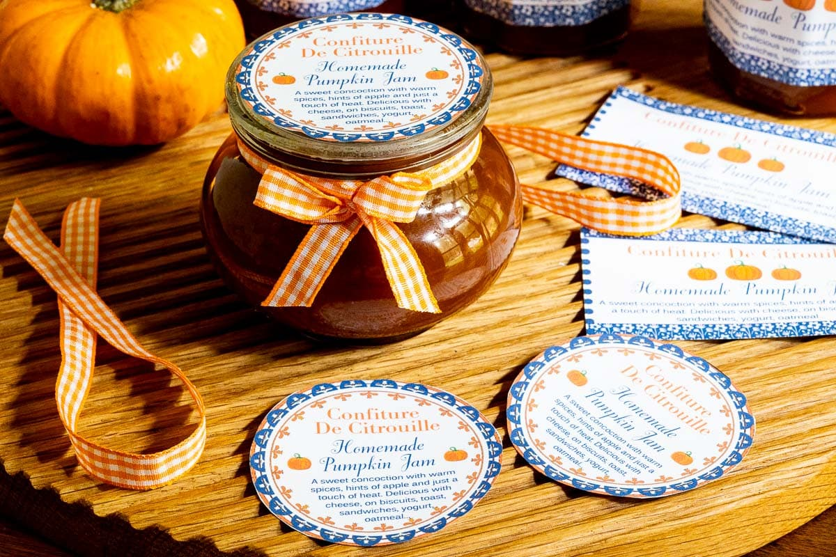 Horizontal closeup photo of a jar of Pumpkin Jam (Confiture De Citrouille) decorated with orange and white checkered ribbon and custom labels for gift giving.