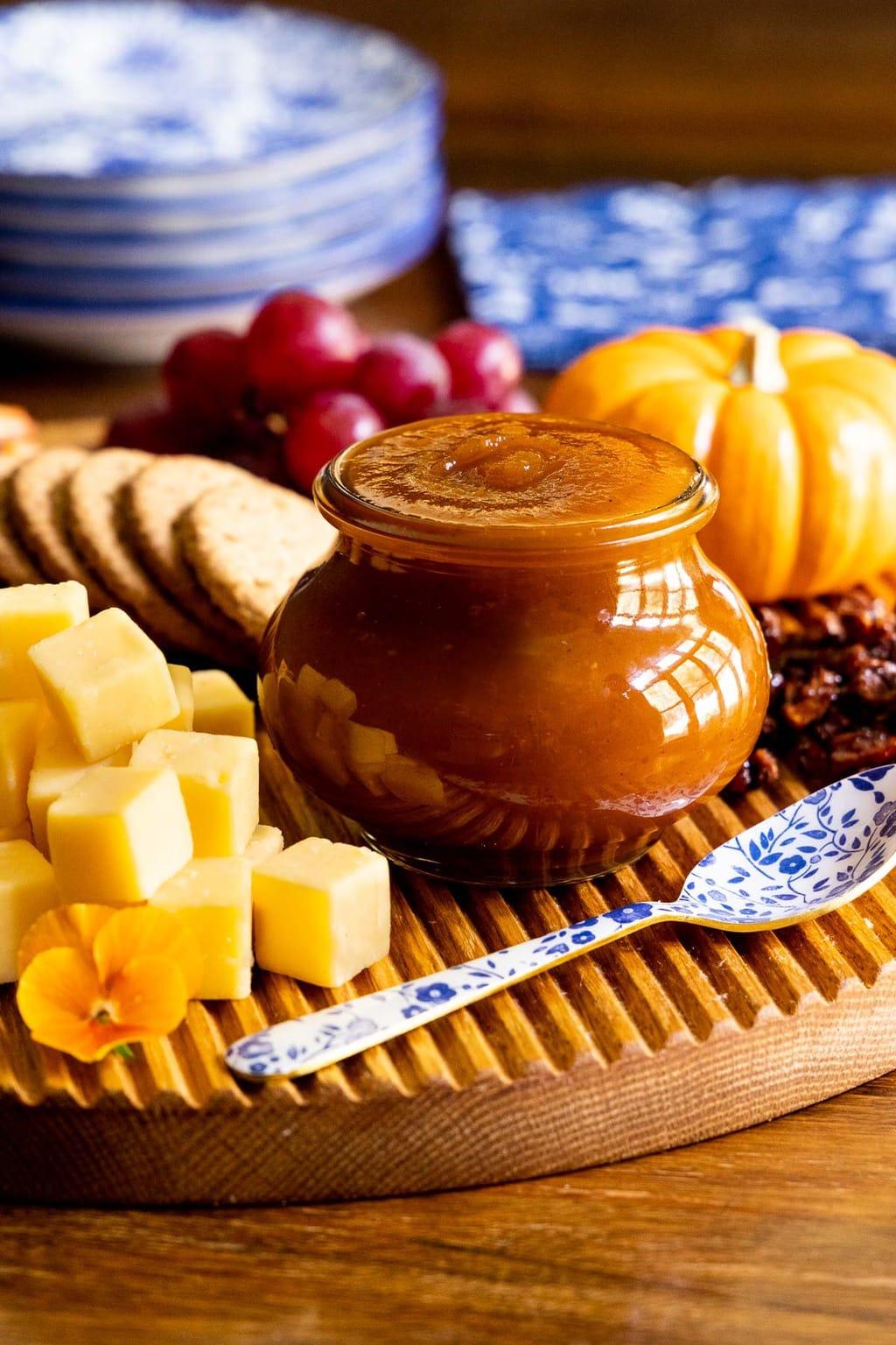 Vertical photo of a fall appetizer tray featuring Pumpkin Jam (Confiture De Citrouille) on a wood cutting board.