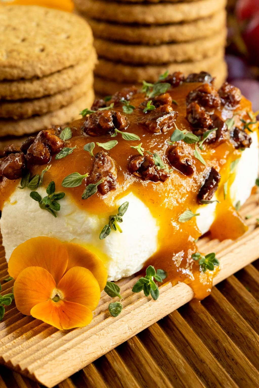 Vertical closeup photo of a log of goat cheese with Pumpkin Jam (Confiture De Citrouille), fresh thyme leaves and candied pecans spread on top.