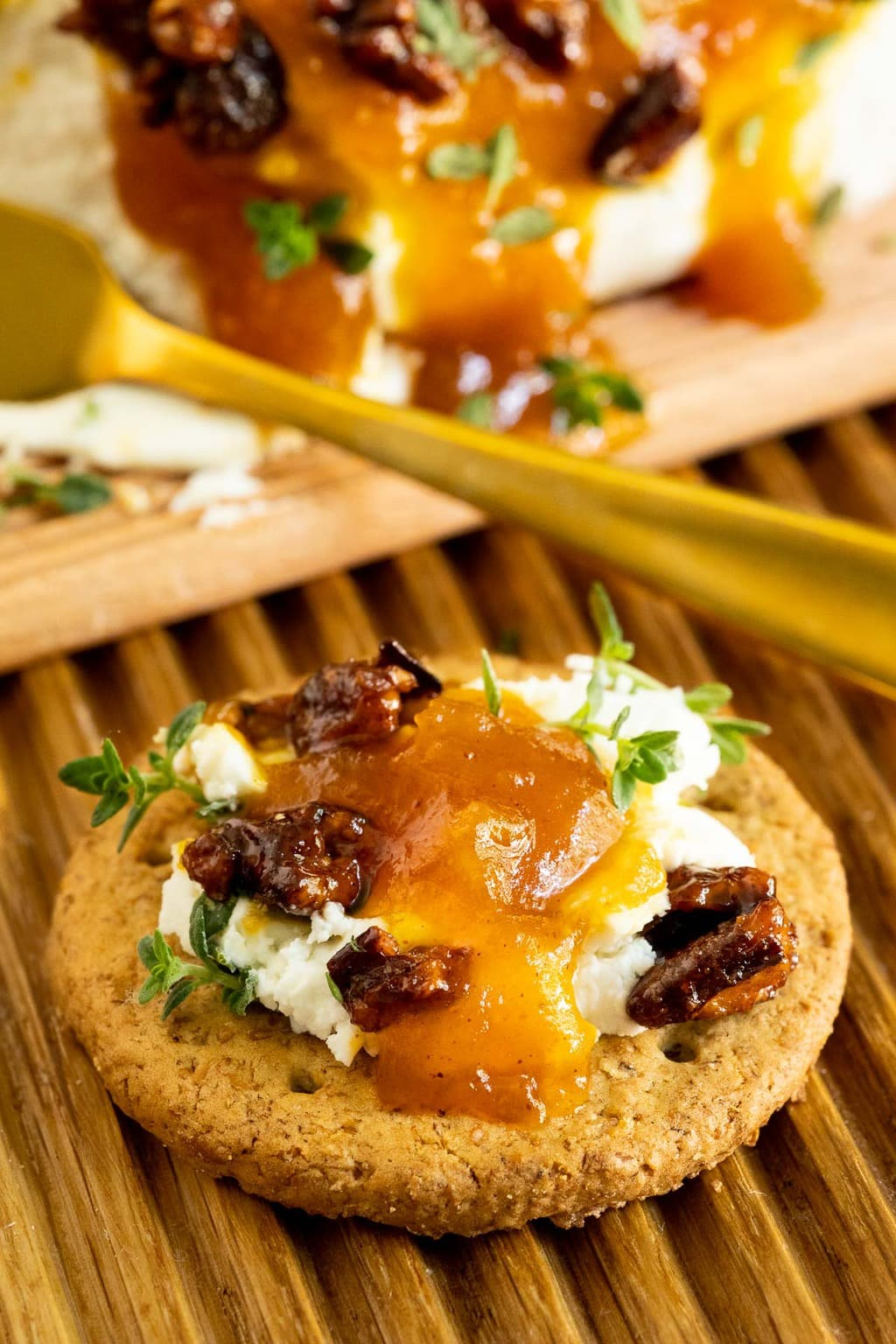 Extreme closeup vertical photo of a cracker with Pumpkin Jam (Confiture De Citrouille), candied pecans and fresh thyme leaves on top.