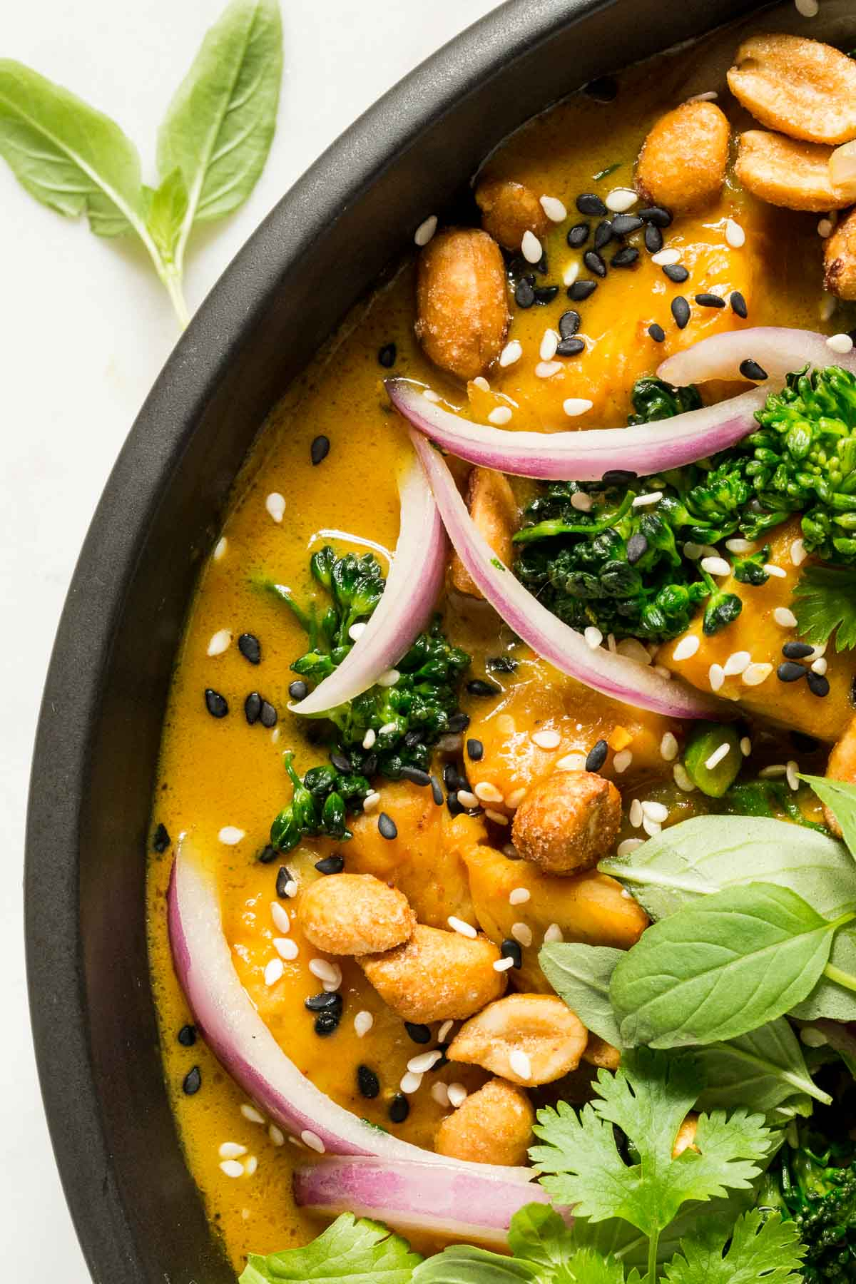 Ultra macro photo of the side of a bowl of 30-Minute Thai Peanut Chicken featuring the peanut sauce.