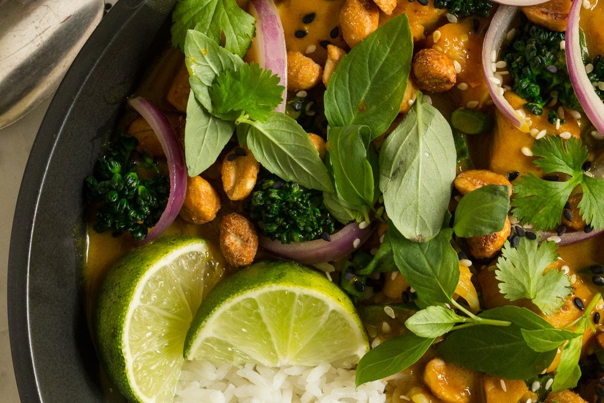 Ultra closeup photo of a bowl of 30-Minute Thai Peanut Chicken garnished with lime wedges and honey roasted peanuts.