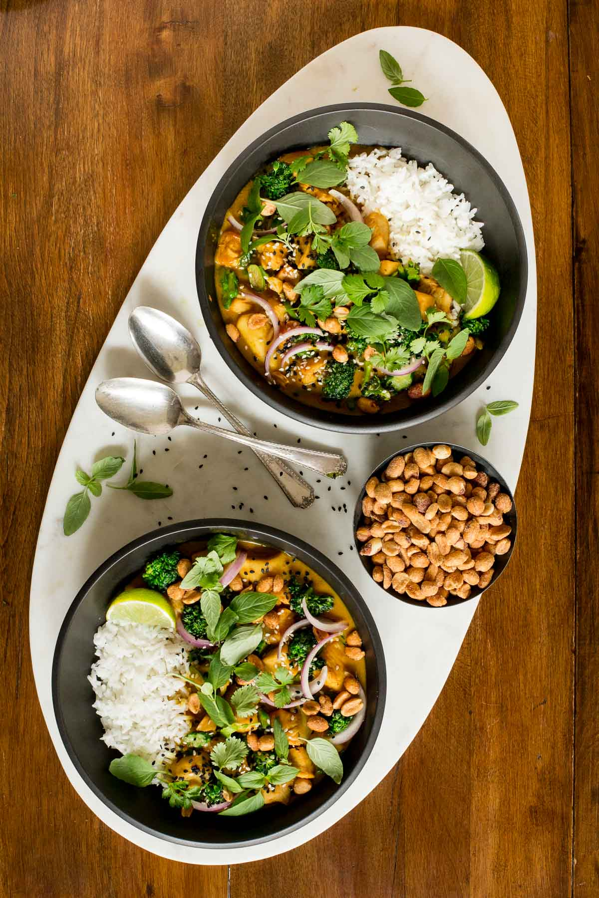 Overhead photo of two black serving bowls of 30-Minute Thai Peanut Chicken surrounded by basil leaves and a bowl of honey roasted basil leaves.