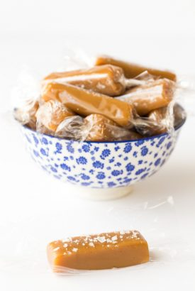 Vertical photo of 8 Minute Microwave Salted Caramels wrapped in plastic in a blue and white bowl.