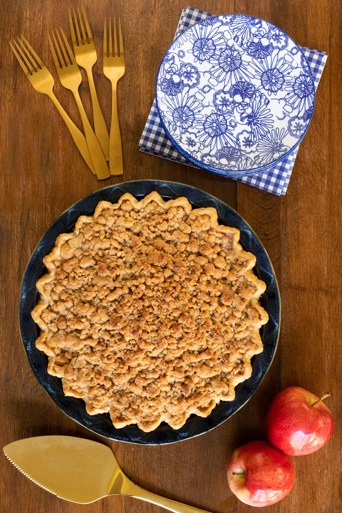 Overhead horizontal photo of a Annie's Easy Apple Pie in a blue ceramic pie pan on a wood table.
