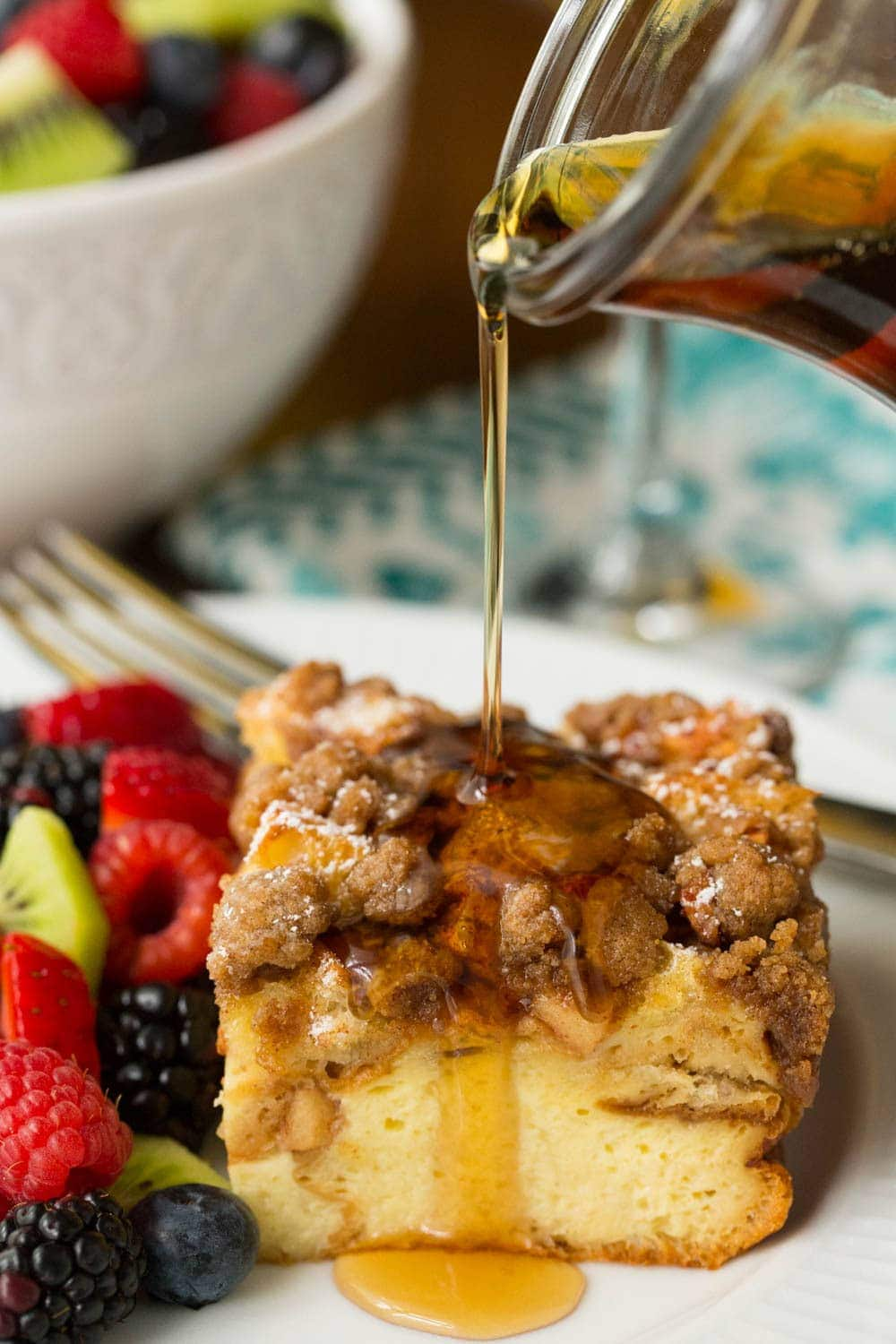 Vertical photo of overnight Apple Cinnamon French Toast Casserole cut into a square with syrup poured on top and a side of fresh fruit.