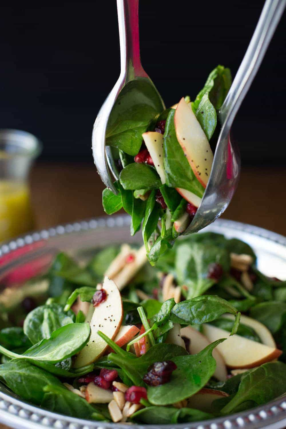 Photo of a pair of tongs lifting a serving of Apple Cranberry Spinach Salad with Honey Cider Dressing from a pewter salad serving dish.