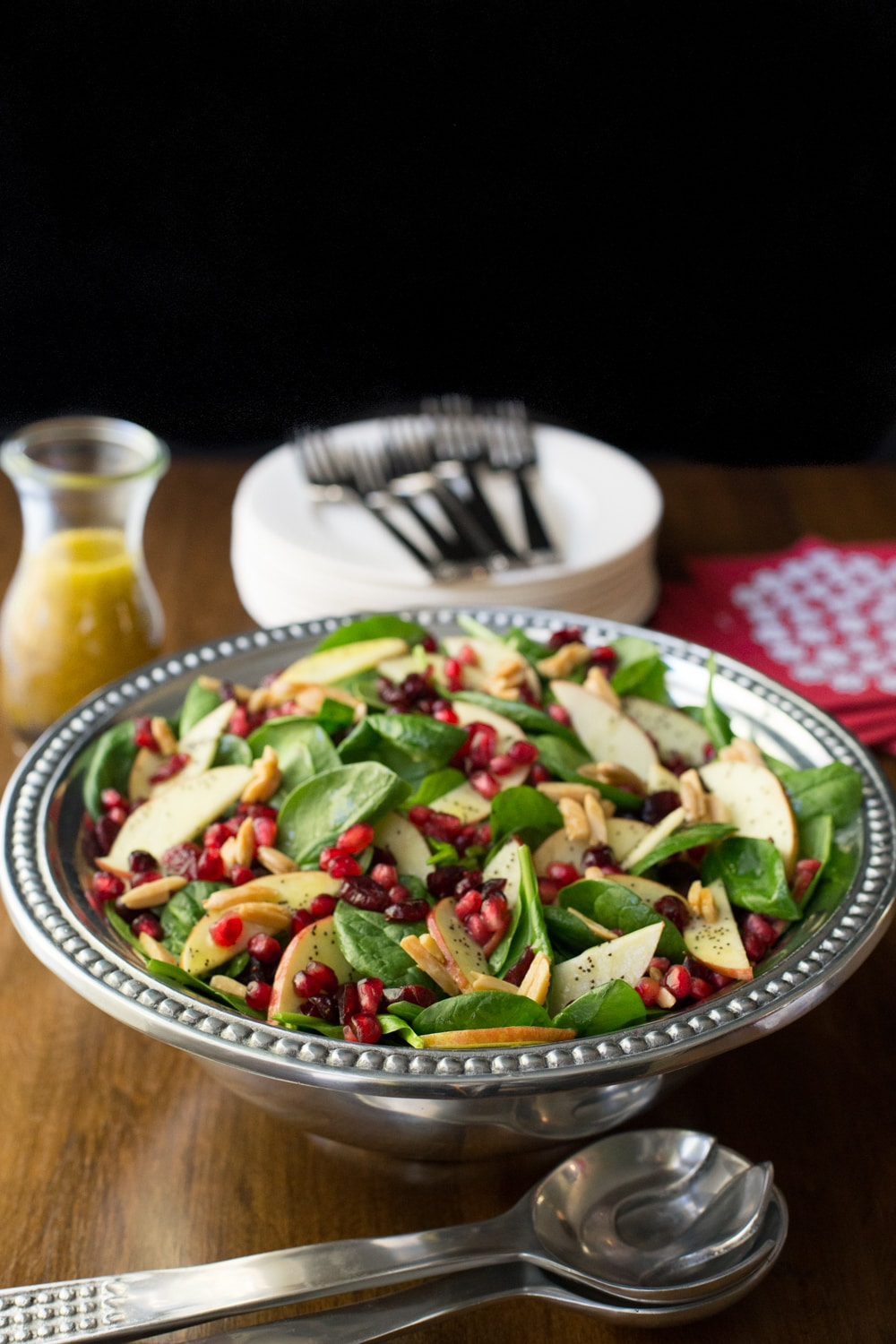 Vertical picture of Apple Cranberry Spinach Salad in a silver bowl with serving dishes and dressing