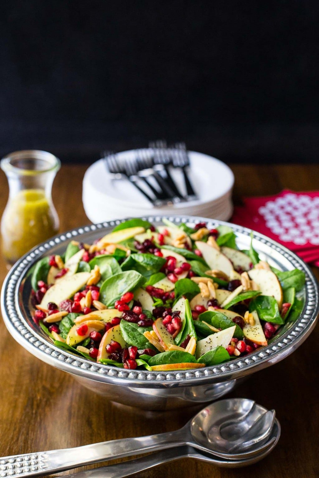 Vertical overall photo of a pewter serving bowl filled with Apple Cranberry Spinach Salad on a wood table.