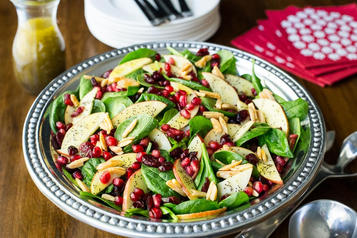 Horizontal photo of a Apple Cranberry Spinach Salad on a pewter serving platter on a wood table.