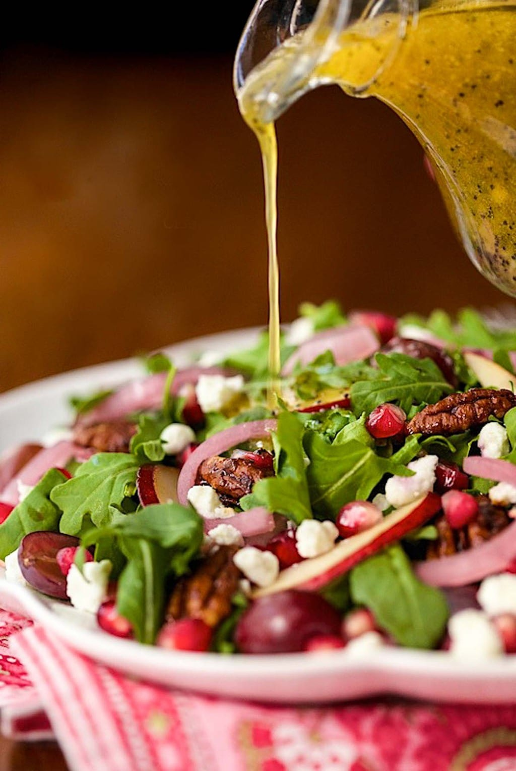 Photo of a patterned serving bowl filled with Arugula, Pomegranate and Pear Salad.