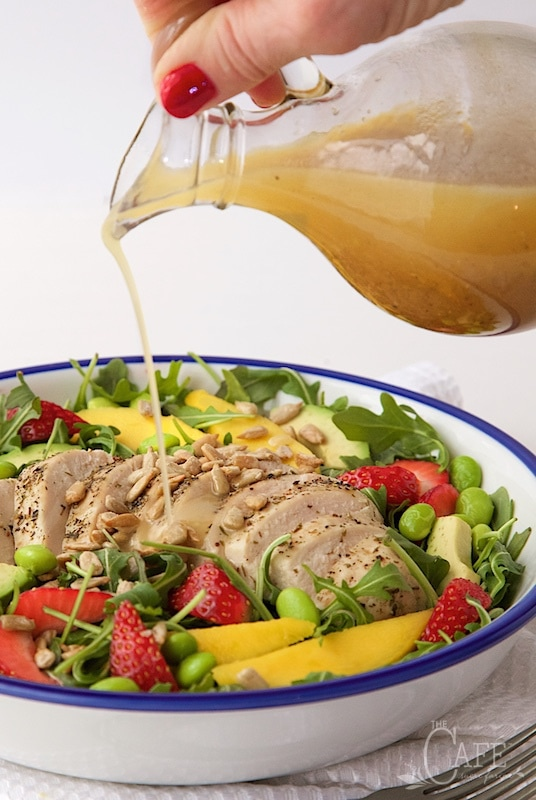 Image of pouring dressing over Arugula Chicken Salad with Honey Lime Dressing.