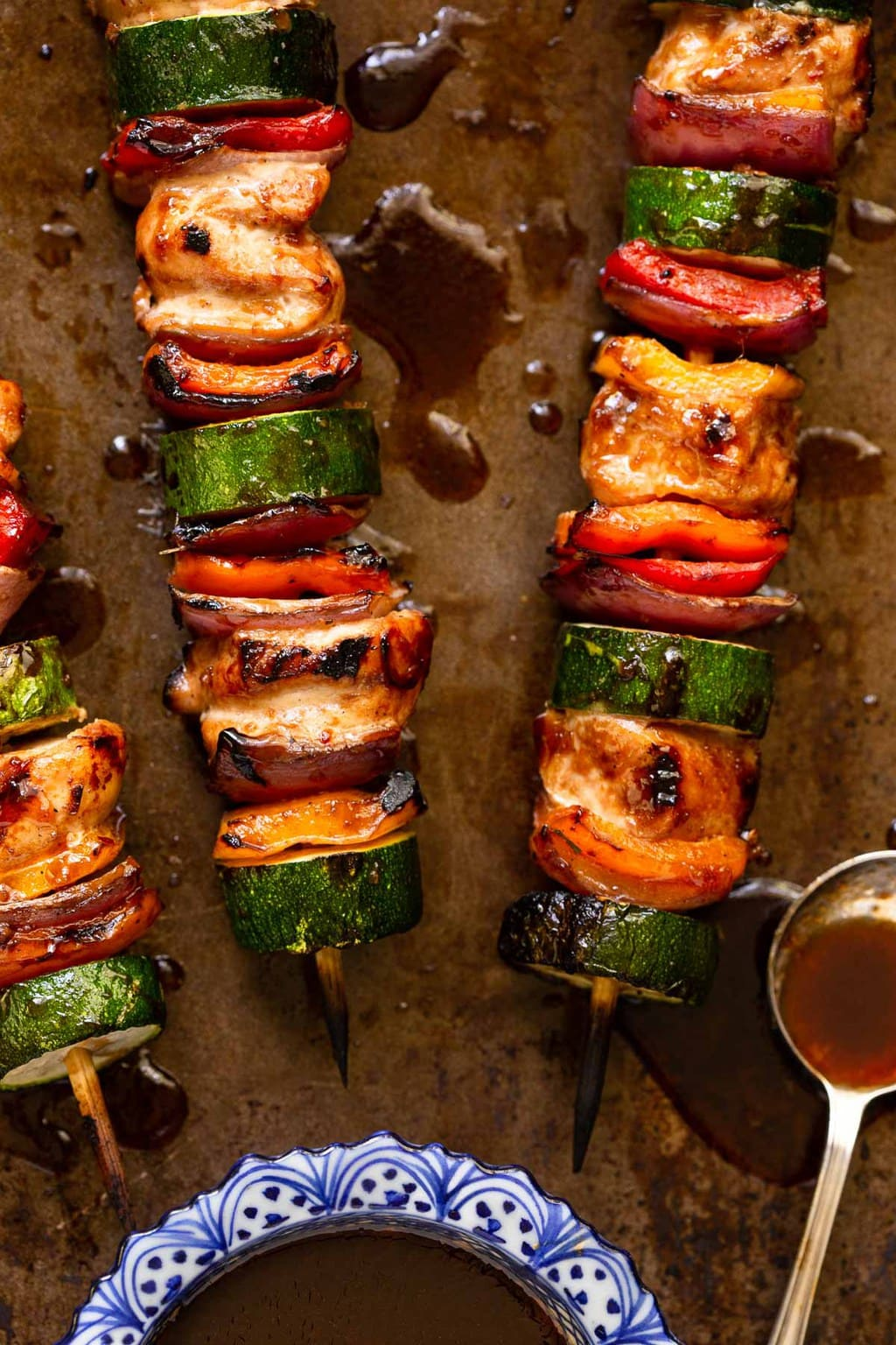 Overhead vertical photo of Asian Grilled Chicken and Veggie Skewers on a sheet pan.