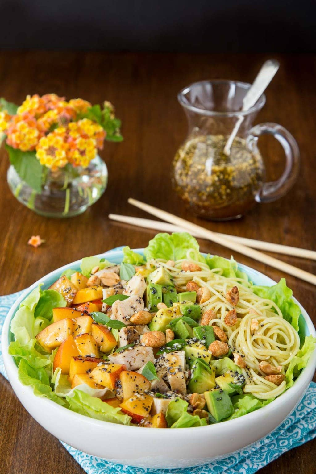 Vertical photo of Asian Chicken and Coconut Curry Noodle Salad in a white bowl on a wood table.