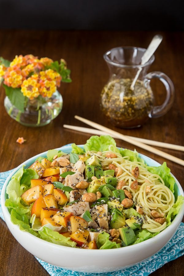 Photo of a bowl of Asian Chicken and Coconut Curry Noodle Salad with a cruet of dressing and a vase of flowers on a wood table.