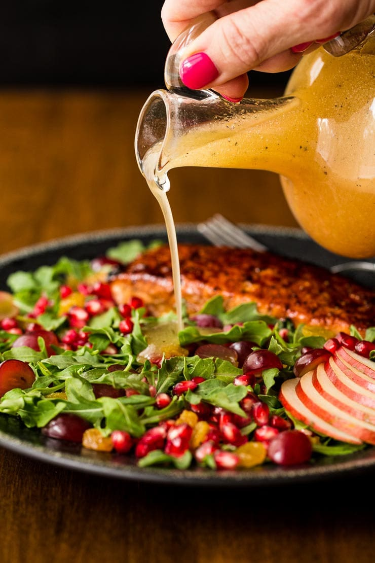 One of 15 Delicious Fall Salads - Photo of a black plate with Asian Glazed Salmon Salad on a wood table with a person pouring salad dressing on it from a glass carafe.