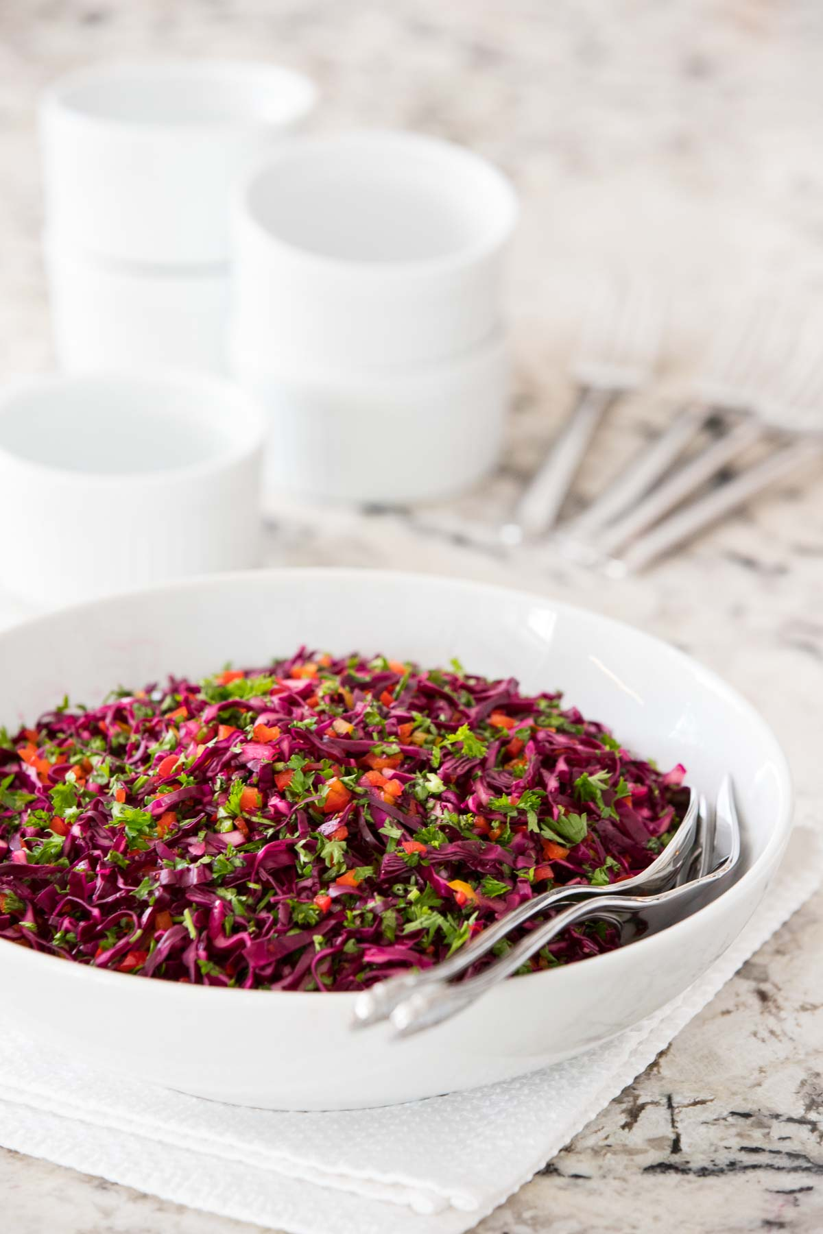 Photo of a serving bowl of Asian Red Cabbage Slaw on a white and black granite countertop.