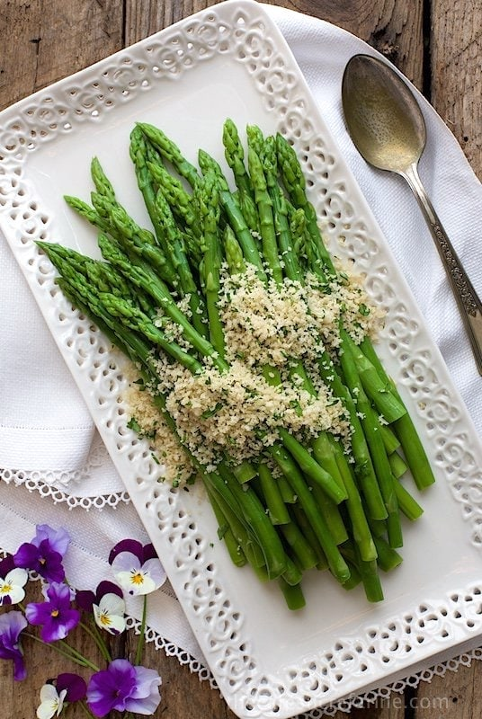 Overhead photo of Asparagus with Lemon Parsley Panko on a white lattice serving platter.