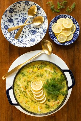 Vertical overhead photo of a pot of Avgolemono (Greek Chicken Pasta Soup) on a wood table.