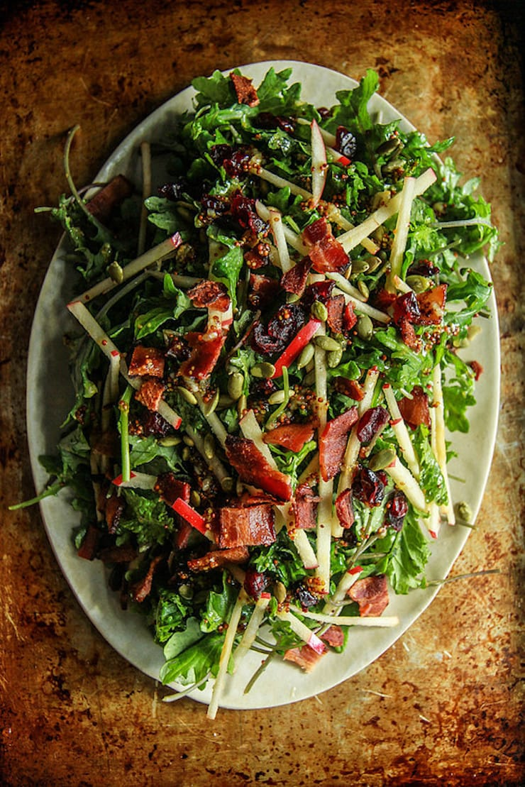 One of 15 Delicious Fall Salads - Overhead photo of a platter of Baby Kale Autumn Salad with Honeycrisp Apples, Bacon, Cranberries and Pepitas on an aged metal surface.