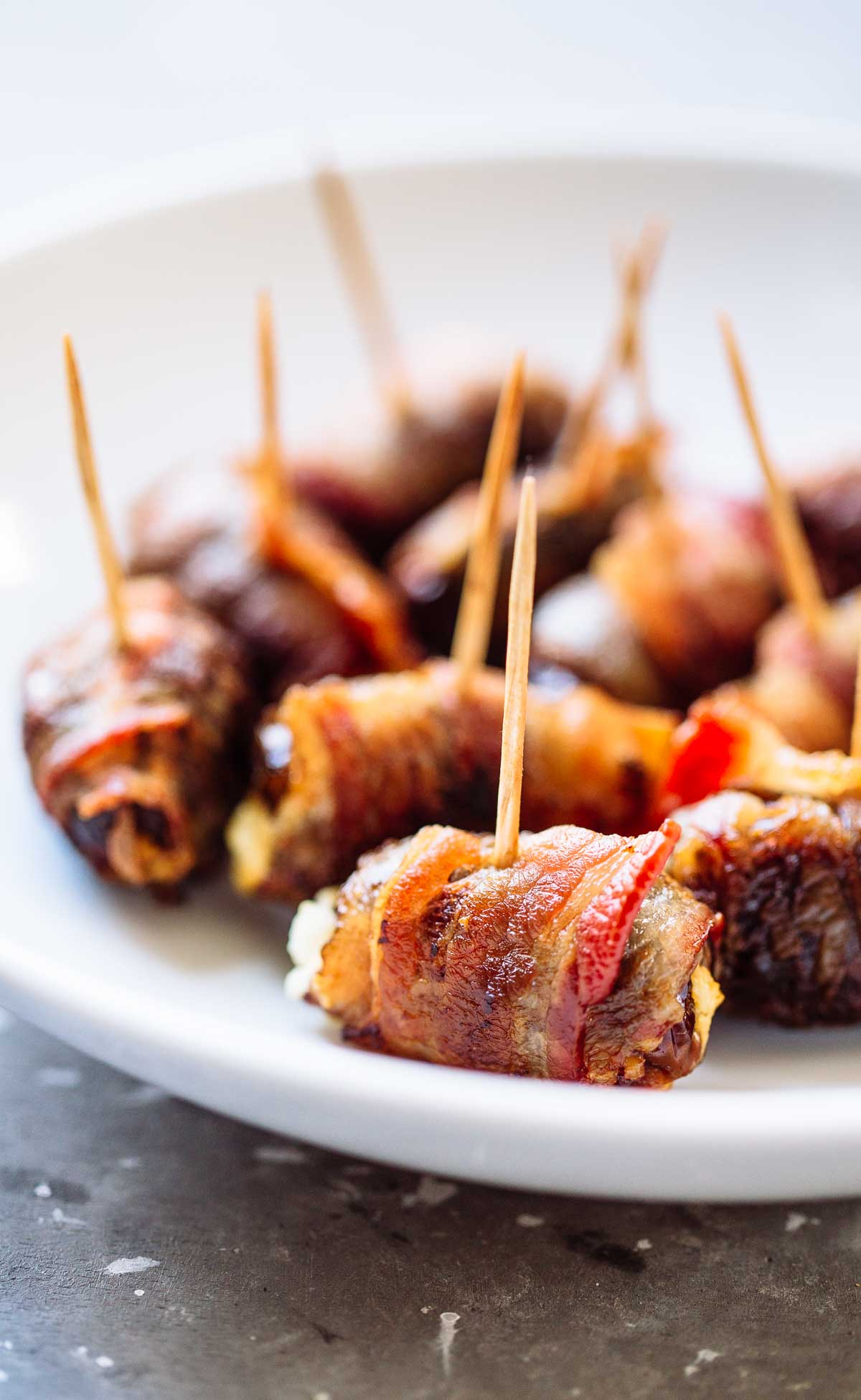 "Photo of a white plate with Bacon Wrapped Dates with Goat Cheese from ""19 Delicious Thanksgiving Sides"" post."