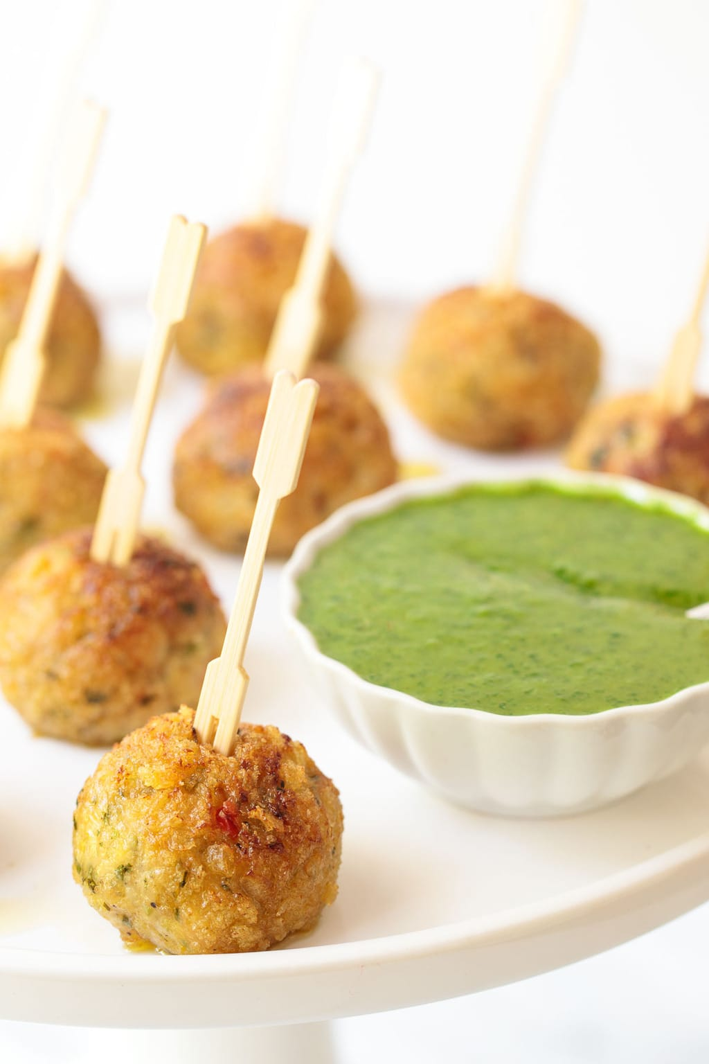 Photo of a white serving platter of Vietnamese Chicken Meatballs with a dish of Lemongrass Cilantro Dipping Sauce.
